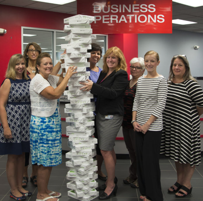UofL's Business Operations team shows off how much paper was saved during the shared services soft launch.