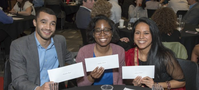 Three medical students hold their envelopes on Match Day.