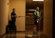 Jeff Marquis uses horizontal poles to help him balance during therapy in the hallway of Frazier Rehab Institute. He is assisted by Curtis Standafer.