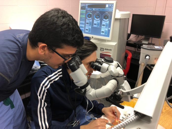 Ophthalmology residents Sidharth Puri, M.D., standing, and Mohammad Ali Sadiq M.D., training in cataract eye surgery using artificial eyes in a 'wet lab' at the University of Louisville