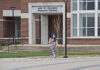 A masked student walks across campus in March, shortly after the COVID-19 pandemic outbreak.